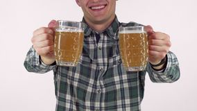 Happy man smiling, holding out two beer mugs to the camera stock image