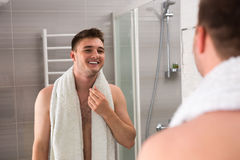 Happy man smiling, holding towel on his shoulders after washing. Procedures while looking in the mirror and standing in the modern tiled bathroom Royalty Free Stock Photo