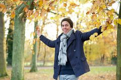 Happy man smiling and holding tree branches with yellow leaves outdoors Stock Image