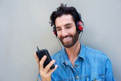 Happy man smiling with mobile phone and headphones Royalty Free Stock Photo