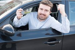 Happy man smiling seated in his car holding key Stock Photo