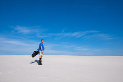 Happy man with a snowboard in hands stands in on the sand dune Royalty Free Stock Photos