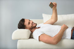 Happy man on a sofa with phone stock images