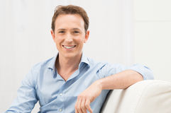 Happy Man On Sofa. Young Man Sitting On Sofa Smiling Royalty Free Stock Photo