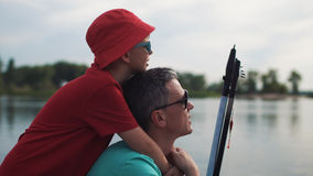 Happy man with son on pier. Son embracing father holding rod on background of pier Stock Images