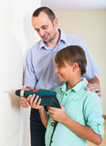 Happy man and son using electric drill Stock Photography