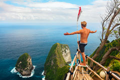 Happy man stand at high cliff viewpoint, look at sea. Family vacation lifestyle. Happy man with raised in air hand stand at viewpoint. Look at beautiful beach stock photos
