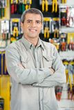 Happy Man Standing Arms Crossed In Hardware Store. Portrait of happy mature man standing arms crossed in hardware store Stock Images