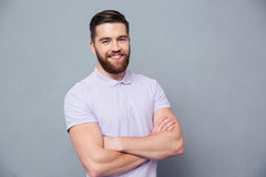 Happy man standing with arms folded. Portrait of a happy casual man standing with arms folded over gray bakground and looking at camera Stock Photos