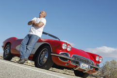 Happy Man Standing beside Classic Car On Road Stock Photo