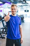 Happy man standing at the gym, showing thumb up. royalty free stock photography