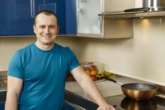 Happy man standing in his kitchen. Leaning on the stove Royalty Free Stock Image