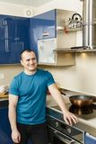 Happy man standing in his kitchen. Leaning on the stove Stock Photo