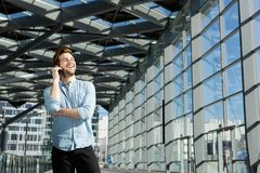 Happy man standing inside building alone with mobile phone Stock Photos
