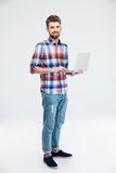 Happy man standing with laptop computer Royalty Free Stock Photo