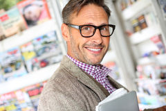 Happy man standing in newsstand Royalty Free Stock Photography