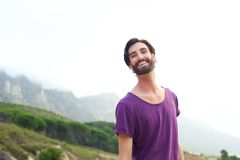 Happy man standing outdoors in purple shirt Stock Images