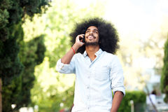 Happy man standing outside in nature with mobile phone Stock Photos