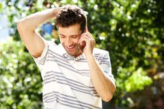 Happy man standing outside and talking on mobile phone. Portrait of happy caucasian man standing outside and talking on mobile phone Stock Photo