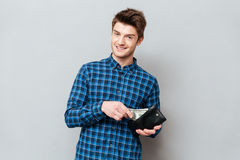 Happy man standing over grey wall holding purse with money. Image of young happy man standing over grey wall and looking at camera while holding purse with royalty free stock photos