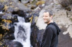 Happy man standing by a small rock waterfall. stock photography
