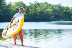 Happy man is standing with a SUP board. In his hands on the beach and looking into the distance. Stand up paddle boarding - awesome active recreation during stock photo