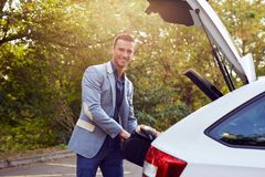 Happy man puts the suitcase in the trunk. Happy man stands by the car and puts the suitcase in the trunk Stock Photography
