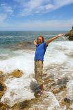 Happy man stands in foamy wave. On beach among awesome rocks. Shot on Cliff Path near Hermanus, Walker Bay, Western Cape, South Africa Royalty Free Stock Images