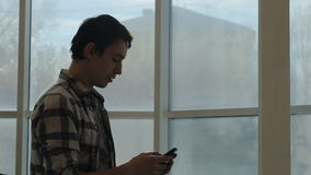 Happy man stands near window and chats on cell phone. Despite fact, it is cold and gloomy outside, he has good mood and shares it with his friends in stock video footage