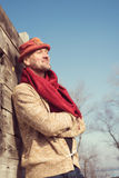 Happy man in a stylish hat is leaning on the wooden fence Stock Photo