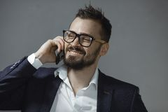 Happy Man in Suit Talking on Smartphone. Cheerful businessman in suit and glassses talking on the phone on a gray background. Portrait of a bearded concentrated royalty free stock photography