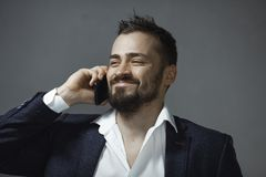 Happy Man in Suit Talking on Smartphone. Cheerful businessman in suit talking on the phone on a gray background. Portrait of a bearded concentrated man speaking stock photography