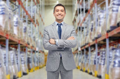Happy man in suit and tie over warehouse. Wholesale, logistic, business, export and people concept - happy man in suit and tie at warehouse over warehouse Stock Image