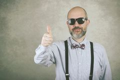 Happy man with sunglasses and bow tie showing thumbs up stock photos
