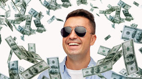 Happy man in sunglasses with falling dollar money Stock Photography