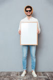 Happy man in sunglasses standing and holding blank white board Royalty Free Stock Photography