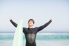 Happy man with surfboard standing on the beach Stock Photo