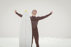 Happy man with surfboard standing on the beach Royalty Free Stock Image