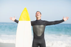 Happy man with surfboard standing on the beach Royalty Free Stock Photos