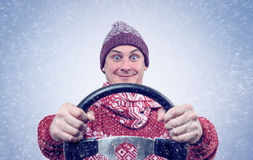 Happy Man in sweater and hat with a steering wheel, snow blizzard. Concept car driver. Royalty Free Stock Photos