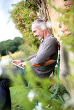 Happy man with a tablet relaxing in garden. Man relaxing in country house on week-end Stock Photography