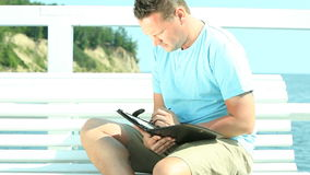 Happy man with tablet by sea Royalty Free Stock Photo