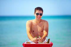 Happy man taking drinks from cooler on beach party Stock Images