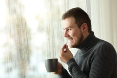 Happy man taking a pill in winter at home Royalty Free Stock Photography