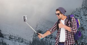 Happy man taking selfie on smart phone against snow covered mountain Royalty Free Stock Image