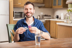 Happy man taking some medicine at home. Handsome Hispanic young man taking some medicine with a glass of water at home and smiling stock image