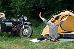 Happy man taking sunbath in forest. Near the camping and motorcycle with sidecar. Relaxation, yoga practicing, unity with nature concept Stock Images