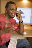 Happy man talking on cell phone. African American young adult talking on cell phone and using computer Stock Images