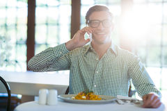 Happy man talking on mobile phone while having a lunch Stock Photos