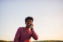 Happy man talking on mobile phone. Outdoors. Low angle and copy space above head royalty free stock photography